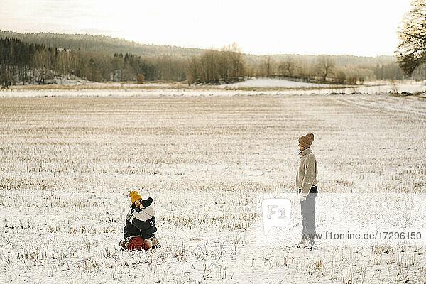 Frau steht in der Nähe Freundin umarmt Tochter auf Schnee