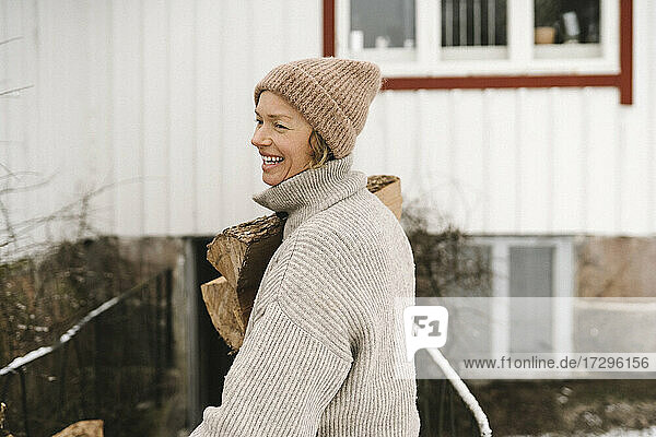 Smiling woman wearing knit hat carrying firewood while looking away
