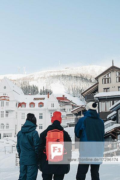 Rückansicht von männlichen und weiblichen Freunden  die im Winter vor einem Gebäude stehen