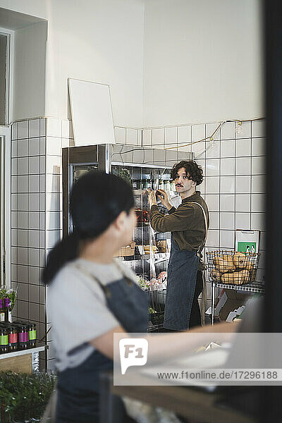 Male and female colleagues talking while working in store