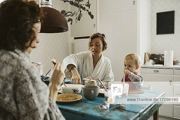 Woman talking with girlfriend while having breakfast at home