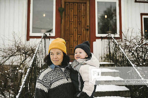 Smiling mother carrying daughter in front of house while looking away during winter