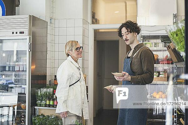 Weiblicher Kunde im Gespräch mit männlichem Unternehmer beim Kauf von Lebensmitteln im Geschäft