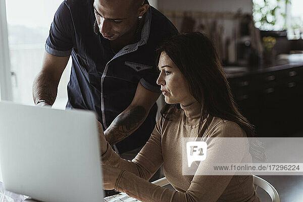 Geschäftsfrau diskutiert mit männlichem Kollegen über Laptop zu Hause