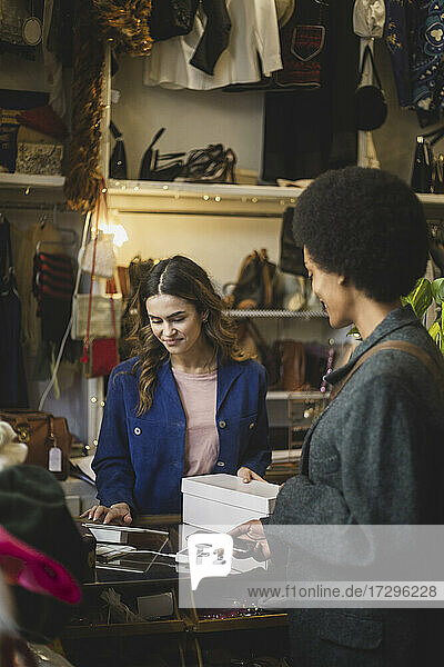 Female customer paying through smart phone at checkout to owner in boutique