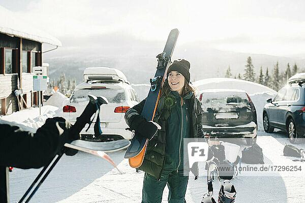 Lächelnde Frau hält Ski  während sie auf einem Parkplatz gegen den Himmel steht