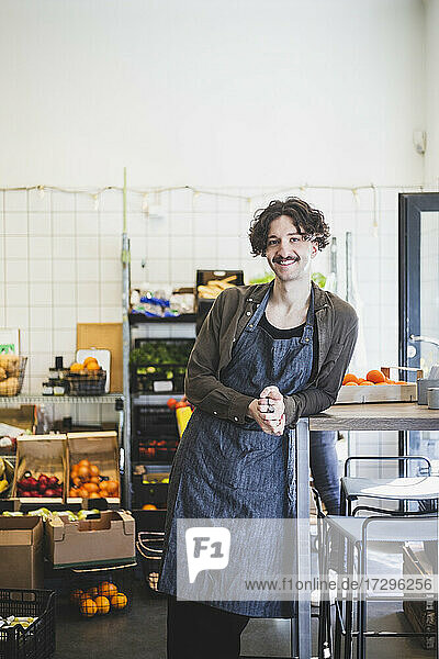 Portrait of smiling male employee with hands clasped standing in store