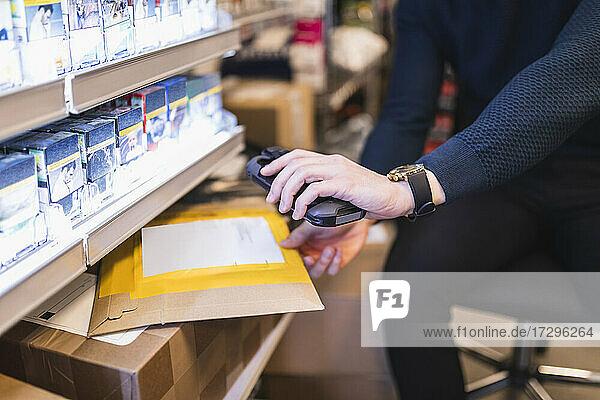 Männlicher Unternehmer mit Barcode-Lesegerät beim Analysieren von Paketen im Geschäft