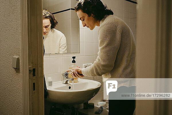 Mittlerer erwachsener Mann beim Händewaschen im Bad zu Hause