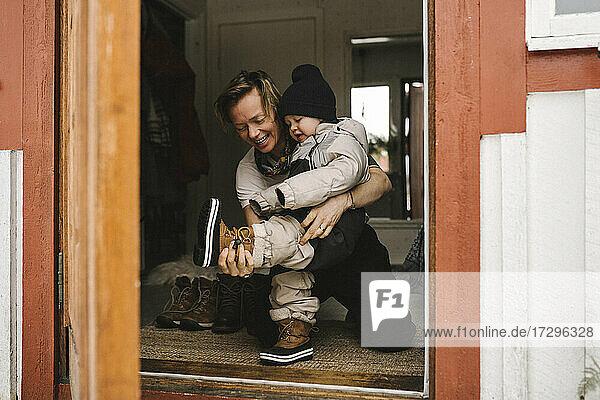 Mother helping daughter wear boot seen through doorway