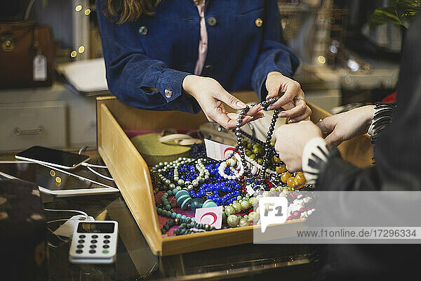 Midsection of owner showing pearl necklaces to customer at store
