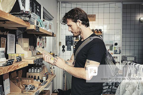 Männlicher Kunde liest Anweisungen auf der Verpackung  während er am Regal eines Bioladens steht