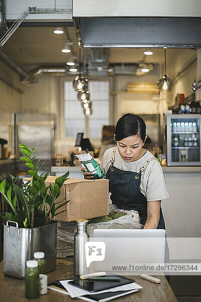 Female employee working laptop while holding food package at store