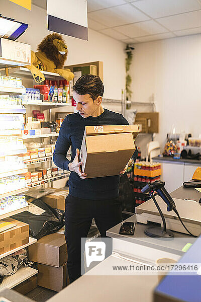 Male store owner carrying boxes while standing at checkout in store