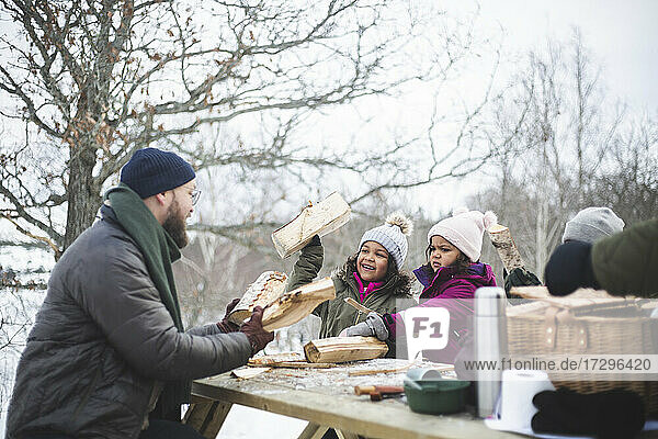 Father and daughter with firewood sitting at picnic table during winter