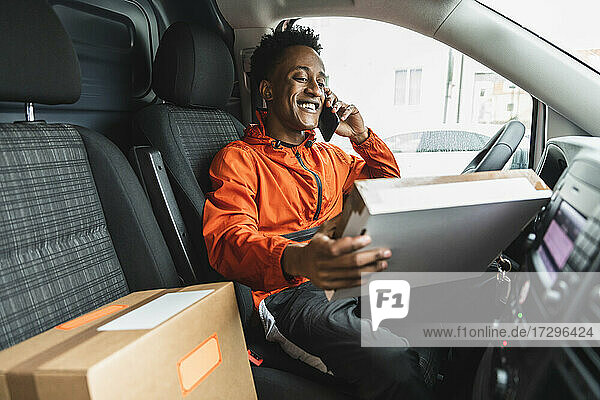 Lächelnde wesentlichen Service Mann Blick auf Paket während des Gesprächs auf Smartphone in Lieferwagen