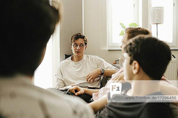 Junge multiethnische männliche Freunde verbringen ihre Freizeit zu Hause