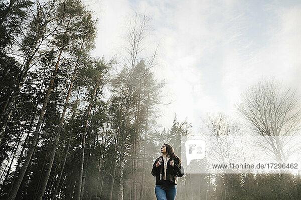 Niedriger Winkel Ansicht der Frau zu Fuß im Wald bei nebligem Wetter