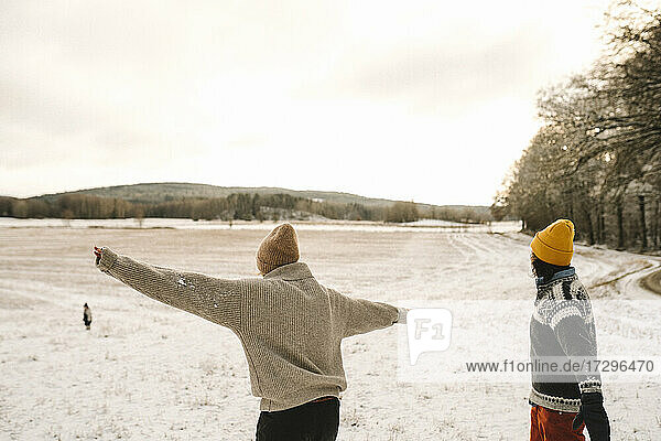 Woman with arms outstretched standing by girlfriend on snow