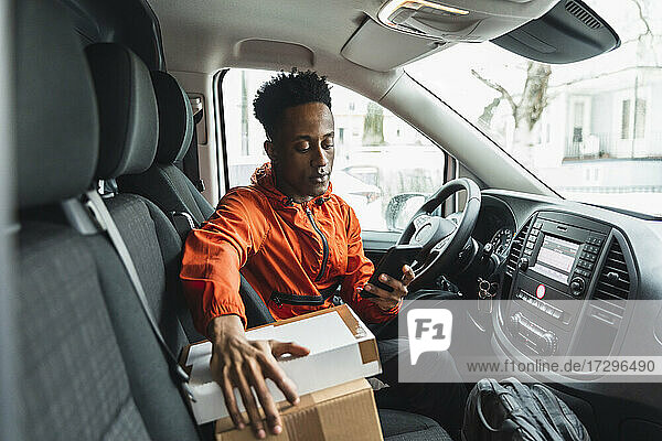 Young male driver using smart phone while sitting in delivery van