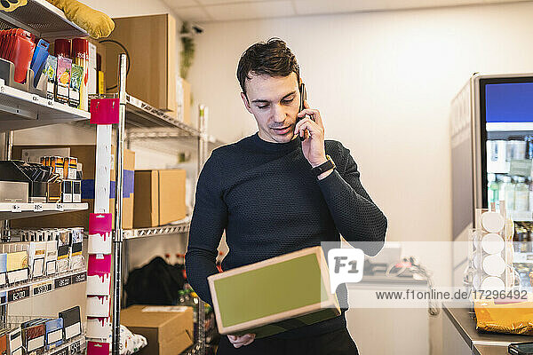 Male owner reading package while talking on phone in store