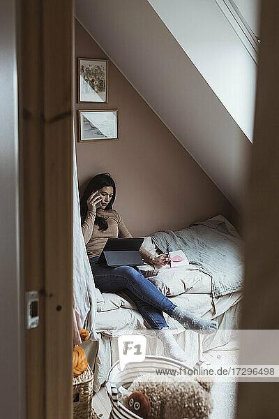 Weibliche Unternehmerin im Gespräch auf Smartphone  während mit digitalen Tablet im Schlafzimmer durch die Tür gesehen