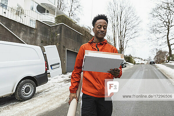Young delivery man carrying packages while walking on road