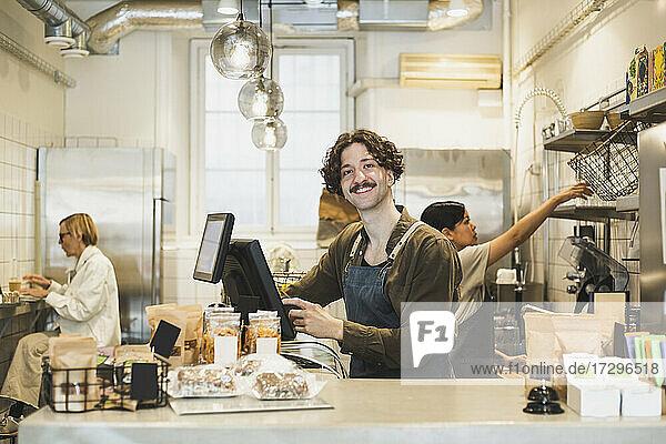 Porträt eines männlichen Besitzers  der in einem Geschäft am Computer arbeitet