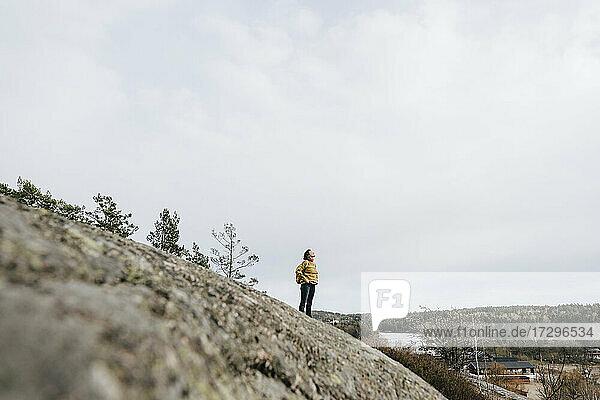 Reife weibliche Entdeckerin stehend auf Berg gegen Himmel