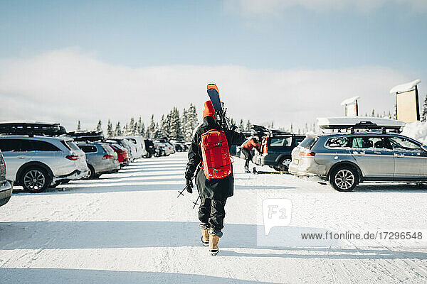 Rear view of woman walking at parking lot during winter
