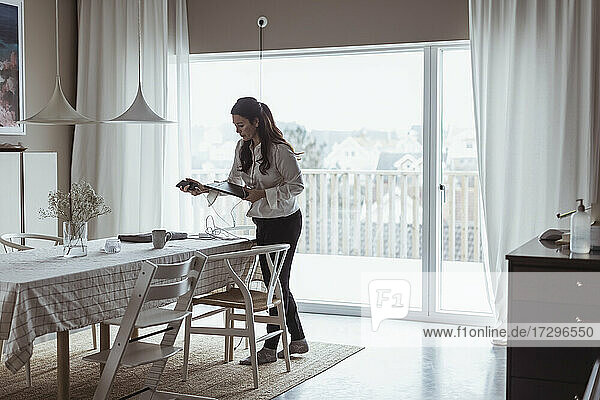 Businesswoman with digital tablet standing at home