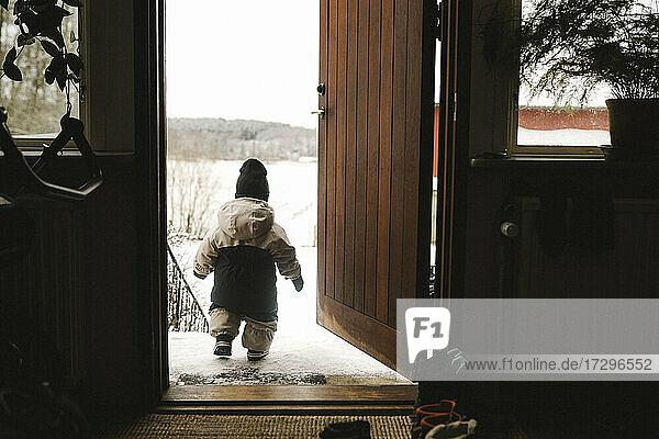 Volle Länge Rückansicht von Baby-Mädchen in warmer Kleidung zu Fuß aus Türöffnung im Winter