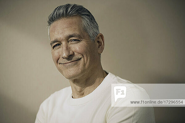 Smiling mature man with gray hair against beige wall