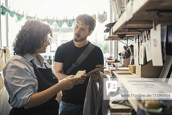Male customer discussing with saleswoman at organic shop