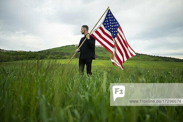 Junger Mann mit amerikanischer Flagge in einem Weizenfeld