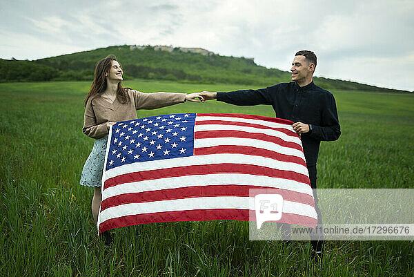 Junges Paar hält amerikanische Flagge in einem Weizenfeld