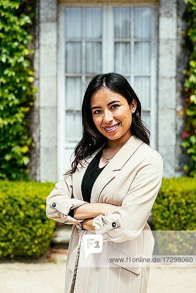 Confident woman in elegant outfit crossing arms standing against plant background