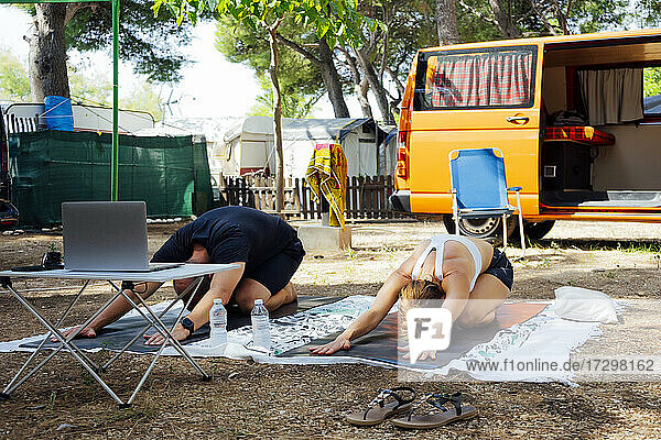Sporty couple practicing yoga with laptop outdoor