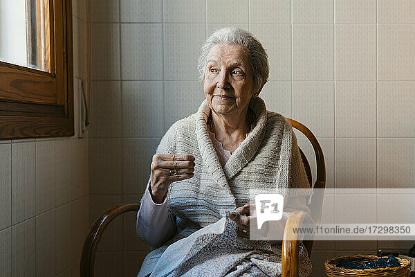 grandmother sews with needle and thread while looking out the window
