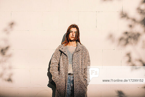 Portrait of transgender woman standing against wall in city