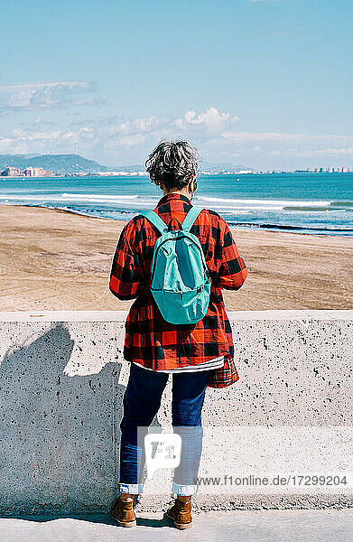 Vertical photo of a middle aged woman from behind with a backpack looking at the sea on a sunny day
