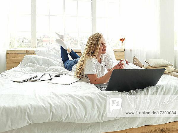 junge blonde Frau öffnet die Kopfhörerbox auf dem weißen Bett liegend