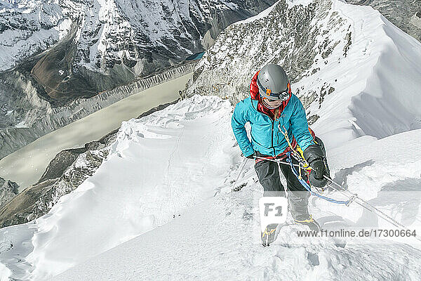 Woman mountaineer with big mittens about to start headwall descent