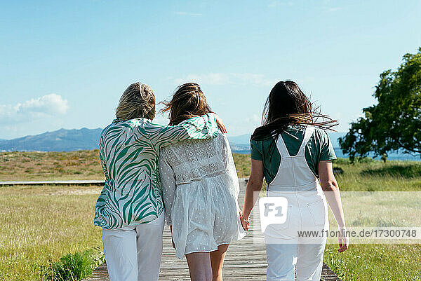 Three anonymous girls walking and looking happy
