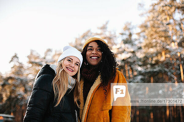 Happy girlfriends standing against trees outdoors during winter