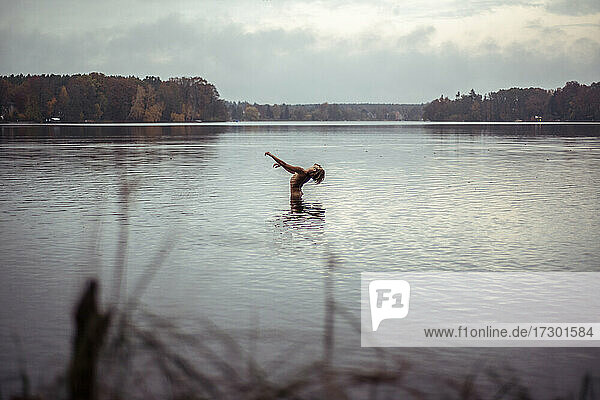 male dancer in natural back arch towards sky in middle of pretty lake