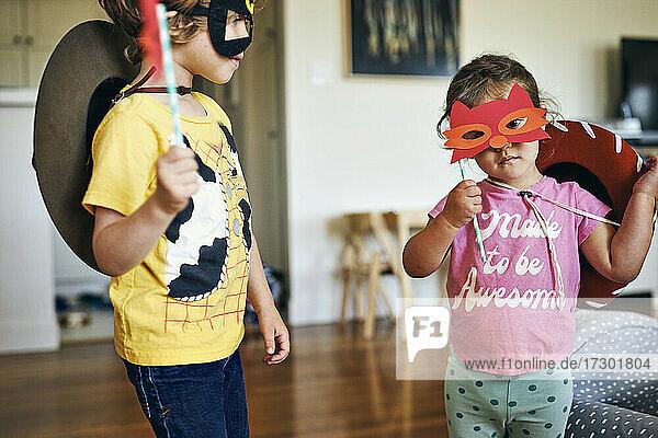 Brother and sister wearing masquerade masks at home