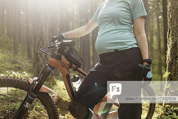 A pregnant young woman enjoys mountain biking in the Columbia River Gorge of Oregon.