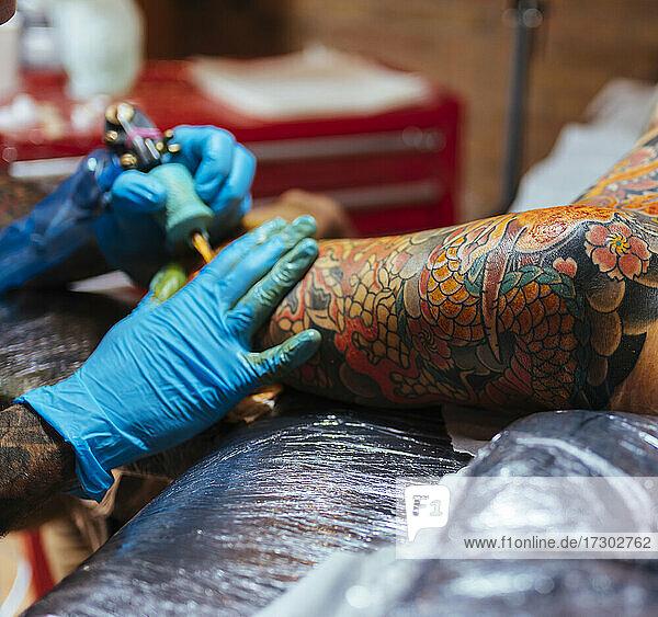 Detail of an artist's hands tattooing a japanese tattoo
