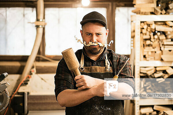 Humor funny portrait of carpenter with shavings mustache and tools